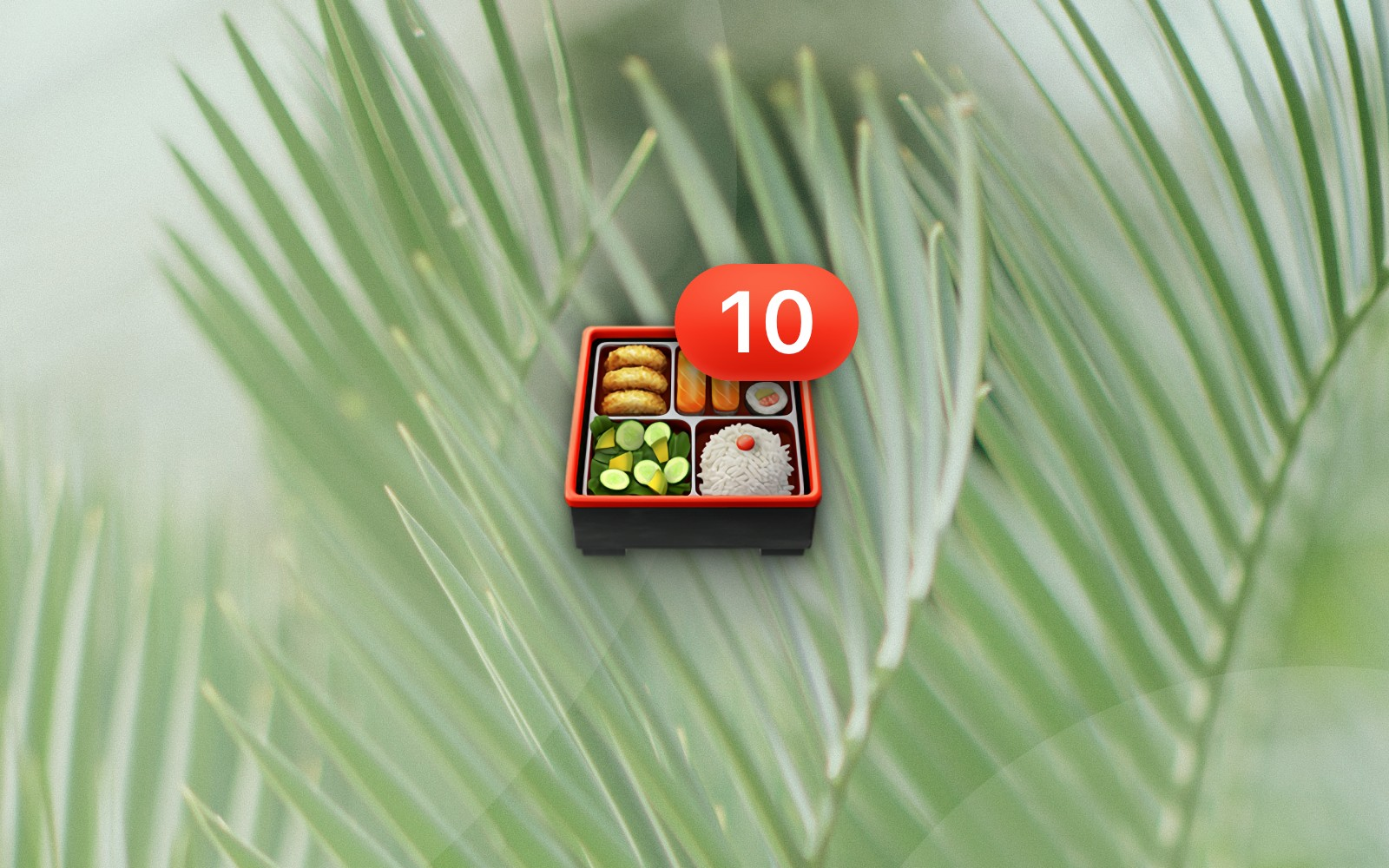Bento box emoji with number 10 badge resting on a palm frond background