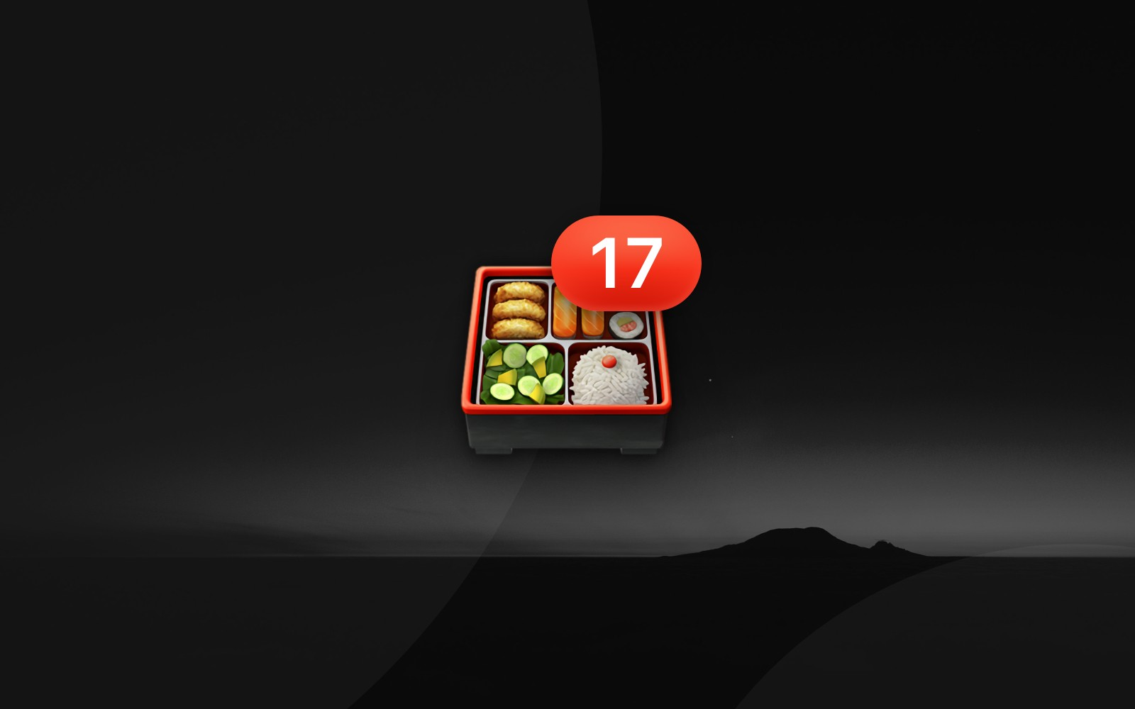 Bento box emoji with number 17 badge resting on a faded sunset